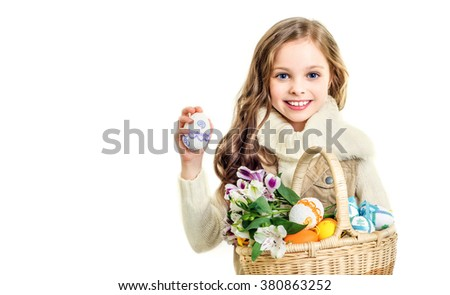 Smiling little girl with basket full of colorful easter eggs and flowers. Easter. Spring.