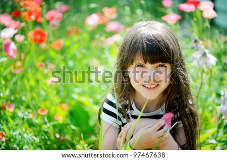 stock photo : Smiling little girl with long dark hair sitting on poppy field