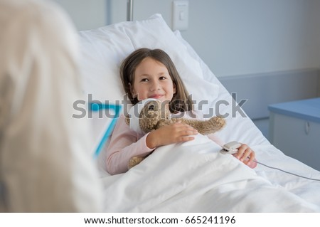 Smiling little girl with oxygen saturated probe resting on hospital bed. Girl patient looking at doctor with a smile. Child and doctor at medical clinic.