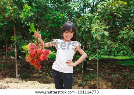 Smiling little girl with Rambutan fruit in her hand and rambutan tree background