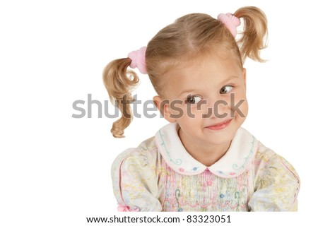 Smiling little girl with two tails wearing a dress on a white background
