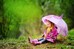 smiling little girl with umbrella in raincoat and boots outdoor