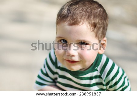 Smiling little handsome boy looks at camera in park. Shallow dof #238951837