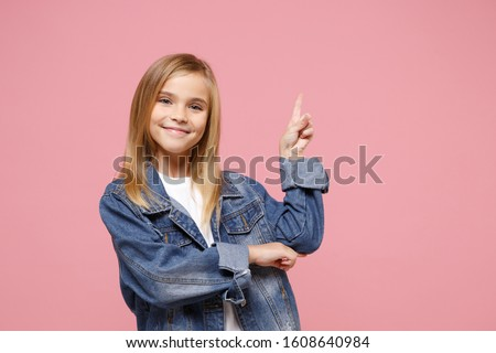 Smiling little kid girl 12-13 years old in denim jacket isolated on pastel pink background children studio portrait. Childhood lifestyle concept. Mock up copy space. Pointing index finger aside up Stock photo ©