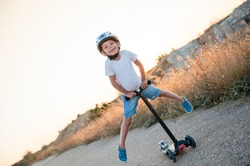 smiling little kid in sport helmet riding on scooter making trick on abandoned road in warm summer sunset