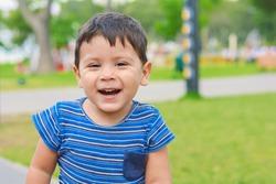 Smiling little latin boy outside.