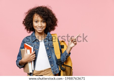 Smiling little smart african kid school girl 12-13 years old in casual clothes backpack hold books point index finger aside on copy space isolated on pastel pink background Childhood education concept Foto stock ©