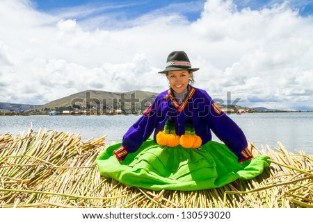 Smiling local girl Sitting on a floating Uros island on the shore of lake Titicaca #130593020
