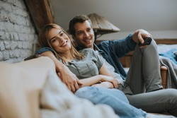 Smiling lovely young couple relaxing and watching TV at home