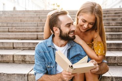 Smiling lovely young couple sitting together on stairs, reading a book, hugging