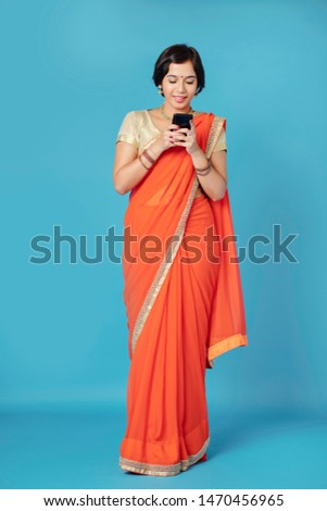 Smiling lovely young Indian woman in beautiful sari dress checking messages on her smartphone