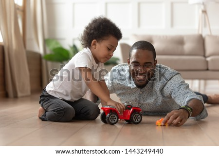 Smiling loving african American dad lying on floor playing with toddler son with toy cars at home, happy caring black father have fun with little kid engaged in funny activity race on automobiles