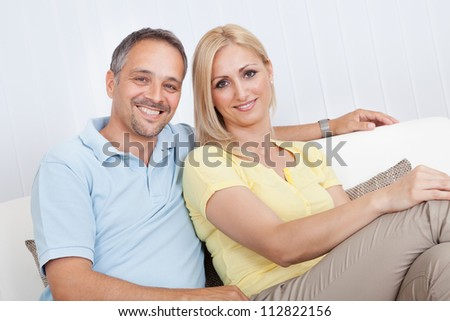 Smiling loving attractive middle-aged couple sitting close together relaxing on a sofa