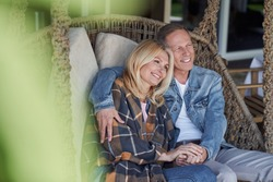 Smiling loving couple is sitting in wicker swings in countryside and holding hands of each other