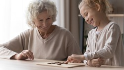 Smiling loving old grandmother and little granddaughter have fun play wooden board game together. Happy mature grandma and small grandchild feel playful with chess or draughts. Hobby concept.