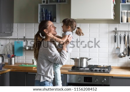 Photo of  Smiling loving single mother holding cute little child daughter having fun together, happy family of young caring mom and excited kid girl laughing playing at home while cooking in the kitchen