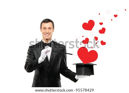 Smiling magician and a red heart shaped objects coming out of a top hat isolated on white background