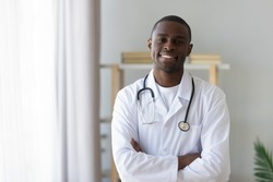 Smiling male african american professional young doctor stand arms crossed wear medical uniform looking at camera, happy confident black man general practitioner with stethoscope in office, portrait