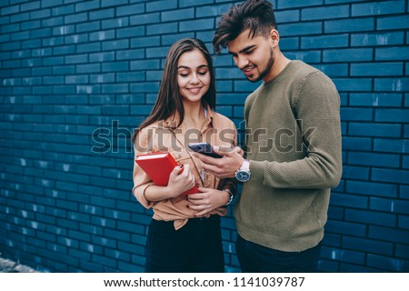 Smiling male and female hipsters having conversation about new modern app for smartphones, positive hipster guy showing his girlfriend photos and videos on mobile phone spending free time together
