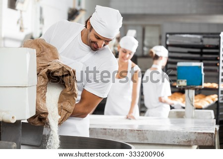 Smiling male baker pouring flour in kneading machine at bakery