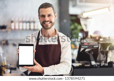 Smiling Male barista holding and showing a digital tablet with empty blank screen at the coffee shop or restaurant cafe. Startup of small business entrepreneur owner. Looking camera. #1378594271