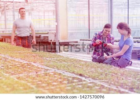 Smiling male botanist looking at female coworkers enjoying coffee break in greenhouse #1427570096