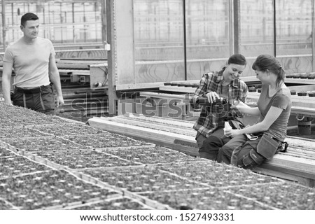 Smiling male botanist looking at female coworkers enjoying coffee break in greenhouse #1527493331