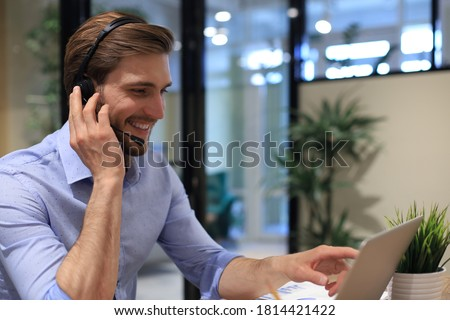 Smiling male business consultant with headphones sitting at modern office, video call looking at laptop screen. Man customer service support agent helpline talking online chat.