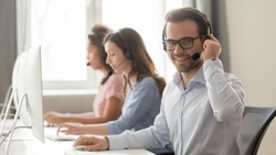 Smiling male call center operator in wireless headset with microphone looking at camera at workplace, businessman agent telemarketer work in customer service helpline support team office, portrait