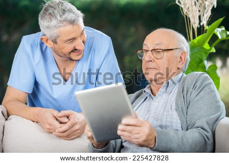 Smiling male caretaker looking at senior man using tablet computer at nursing home porch