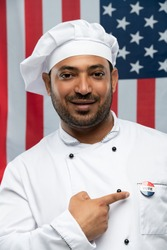 Smiling male chef of restaurant in uniform pointing at vote insignia on chest while standing in front of camera against stars-and-stripes