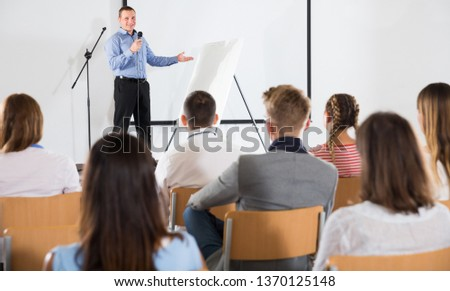 Smiling male coach giving presentation for adult audience in lecture hall 