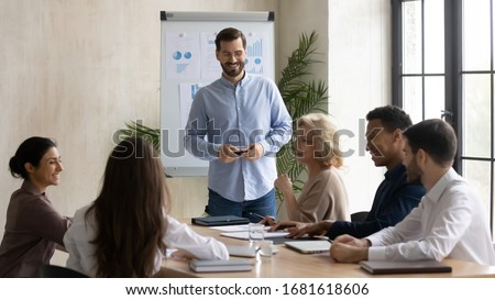 Smiling male coach joke make whiteboard presentation for multiracial businesspeople at briefing, happy diverse colleagues have fun laugh discussing business ideas brainstorming at team meeting