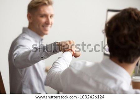 Smiling male colleagues fist bumping at workplace, happy friends greeting, partners sharing success, employees celebrating good teamwork result, workers supporting motivation concept, close up view