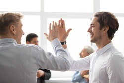 Smiling male colleagues giving high five in office, happy motivated young men coworkers celebrating victory, goal achievement win or successful teamwork, sharing good result, friends greeting concept