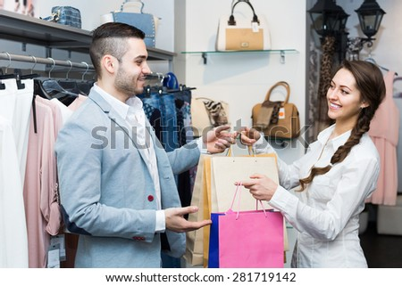 Smiling male customer with cheerful female shop assistant at boutique. Focus on man