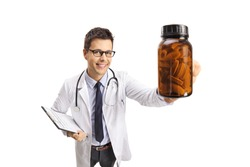 Smiling male doctor holding a bottle of pills isolated on white background