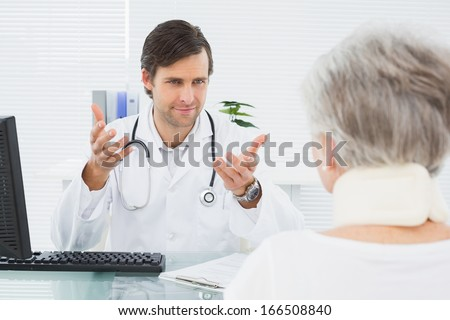 Smiling male doctor listening to senior patient with concentration at the medical office
