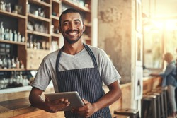 Smiling male entrepreneur in his coffee shop holding digital tab