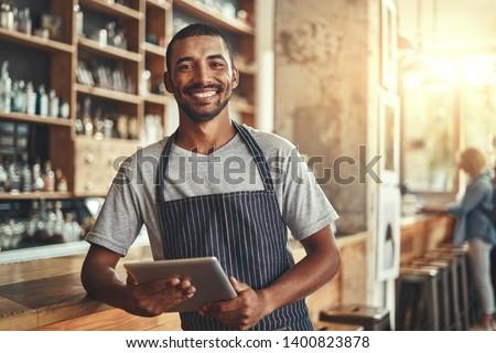Smiling male entrepreneur in his coffee shop holding digital tab