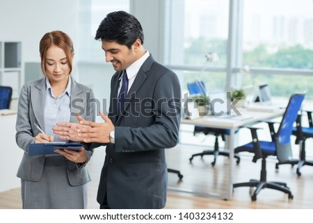 Smiling male executive telling about his plans on work day to his secretary and she writing it in her document while they standing at office stock photo