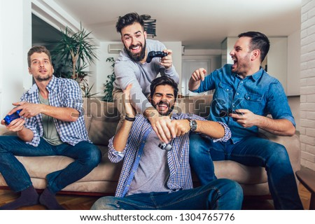 Smiling male friends playing video games at home and having fun. #1304765776