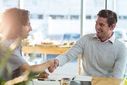 Smiling male friends shaking hands in café