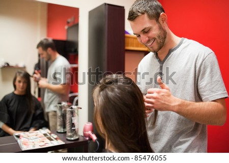 Smiling male hairdresser cutting hair with scissors
