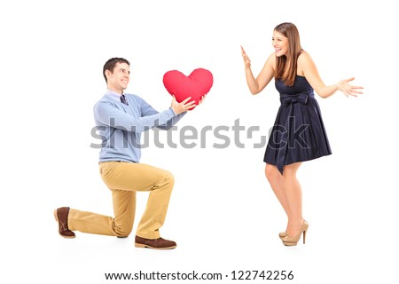 Smiling male kneeling with red heart and surprised woman isolated on white background