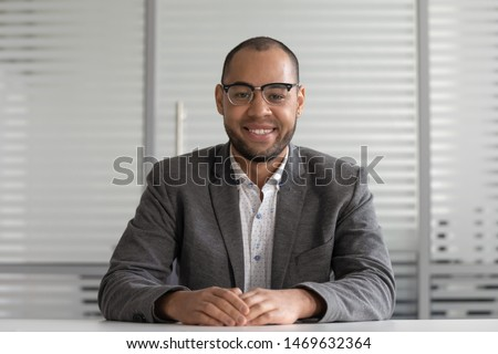 Smiling male mixed race ethnicity employee sit at office desk look at camera shooting video tutorial, happy positive biracial man worker posing for picture at workplace, record online training course