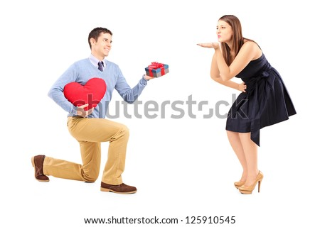 Smiling male on kneel with a red heart giving and a present to a woman blowing him a kiss isolated on white background