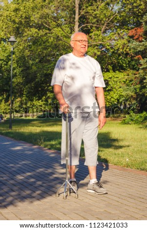 Smiling male pensioner enjoying walk in park with stick #1123421033