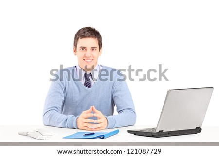Smiling male posing on a desk with laptop and other office staff isolated on white background