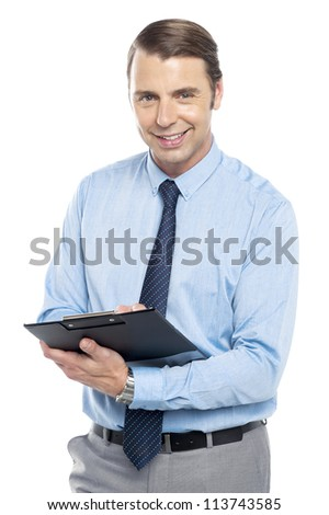 Smiling male secretary holding a clipboard ready to take down notes from his boss
